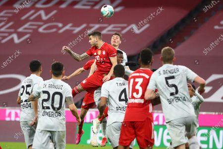 Bayern's Lucas Hernandez, center, jumps for a header, during the German Bundesliga soccer match between Bayern Munich and Bayer Leverkusen at the Allianz Arena stadium in Munich, Germany