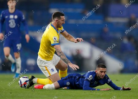Chelsea's Hakim Ziyech, right, duels for the ball with Brighton's Lewis Dunk during the English Premier League soccer match between Chelsea and Brighton and Hove Albion at Stamford Bridge Stadium in London