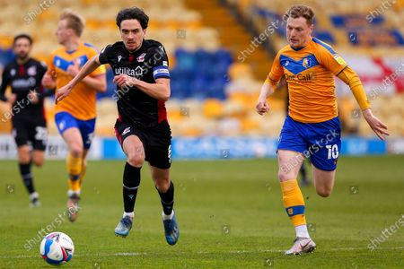 Alex Gilliead of Scunthorpe United and George Maris of Mansfield Town chase down the ball