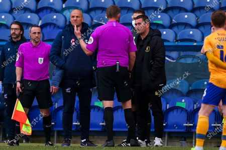 The referee talks with Scunthorpe United manager Neil Cox and Mansfield Town manager Nigel Clough after a drone stops play