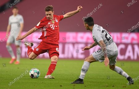 Bayern's Joshua Kimmich (L) in action against Leverkusen's Charles Aranguiz (R) during the German Bundesliga soccer match between FC Bayern Munich and Bayer 04 Leverkusen in Munich, Germany, 20 April 2021.
