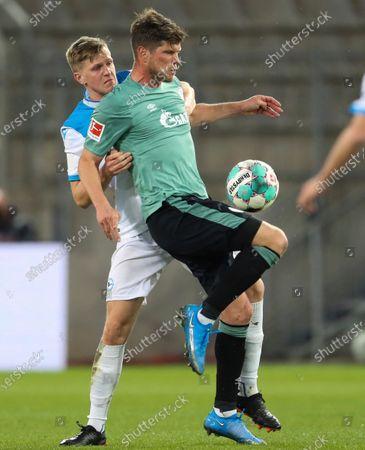 Bielefeld defender Joakim Nilsson, left, fights for the ball with Schalke striker Klaas Jan Huntelaar during their German Bundesliga soccer match at Schuco Arena in Bielefeld, Germany