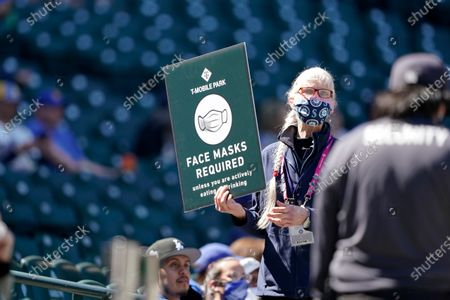 An usher holds up a sign reminding fans to wear face masks during a baseball game between the Seattle Mariners and the Los Angeles Dodgers, in Seattle