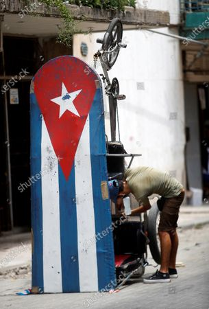 A man repairs a bikecab decorated with the Cuban flag, in Havana, Cuba, 20 April 2021. Cuban President Miguel Diaz-Canel Bermudez was elected First Secretary at Cuba's communist party congress on 19 April 2021, succeeding Raul Castro who was stepping down as the leader of the party.