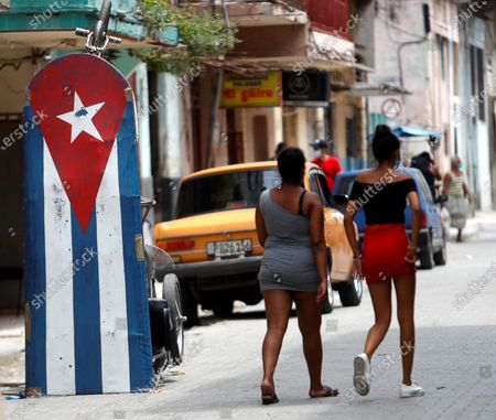 Two women walk next to a bikecab decorated with the Cuban flag, in Havana, Cuba, 20 April 2021. Cuban President Miguel Diaz-Canel Bermudez was elected First Secretary at Cuba's communist party congress on 19 April 2021, succeeding Raul Castro who was stepping down as the leader of the party.