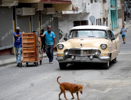 Stock Photo of Two men carry a piece of furniture on a wheelbarrow in Havana, Cuba, 20 April 2021. Cuban President Miguel Diaz-Canel Bermudez was elected First Secretary at Cuba's communist party congress on 19 April 2021, succeeding Raul Castro who was stepping down as the leader of the party.