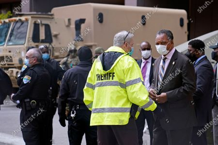 The Rev. Jesse Jackson, right, visits with a deputy after entering the secure Hennepin County Government Center, in Minneapolis, for the verdict before jurors found former Minneapolis police Officer Derek Chauvin guilty on all counts of murder and manslaughter in the death of George Floyd during an arrest last May in Minneapolis