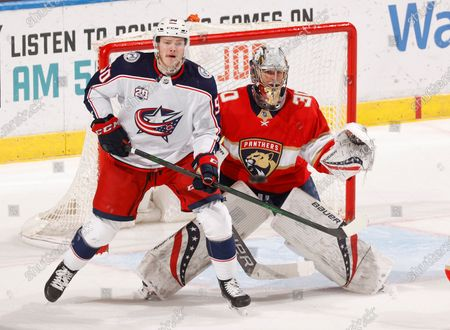 Florida Panthers goaltender Spencer Knight (30) defends the net with Columbus Blue Jackets left wing Eric Robinson (50) waiting for a tip-in attempt during the second period of an NHL hockey game, in Sunrise, Fla