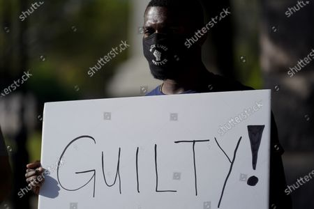 """Mike James stands with a sign reading """"Guilty"""" at the Texas Capitol, in Austin, Texas, after the guilty verdict in the murder trial of former Minneapolis police Officer Derek Chauvin was announced in the death of George Floyd"""