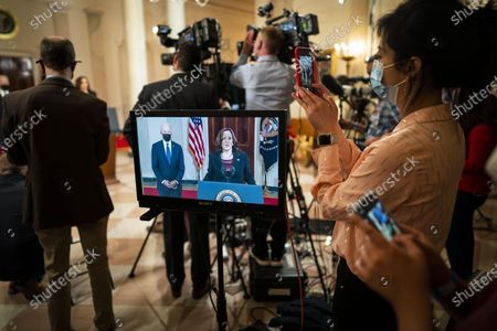 Stock Photo of Members of the press gather to film US President Joe Biden and US Vice President Kamala Harris (both on screen) delivering remarks after former Minneapolis Police Department Police Officer Derek Chauvin was found guilty on all counts in the death of George Floyd, at the White House in Washington, DC, USA, 20 April 2021.