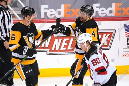 Pittsburgh Penguins' Mike Matheson (5) celebrates his goal with Cody Ceci (4) as New Jersey Devils' Jesper Boqvist (90) skates back to his bench during the first period of an NHL hockey game in Pittsburgh