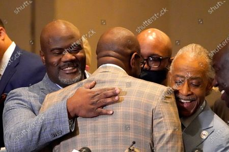 Philonise Floyd, center, brother of George Floyd, is hugged by his brother Rodney Floyd, left, and Rev. Al Sharpton during a news conference after the verdict was read in the trial of former Minneapolis Police officer Derek Chauvin, in Minneapolis