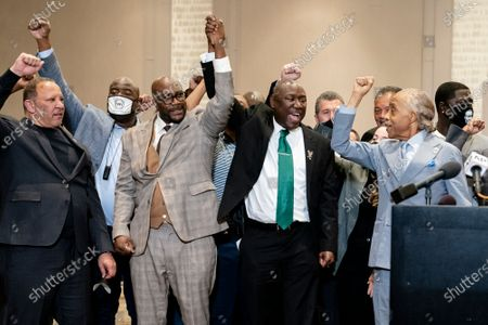 Philonise Floyd, brother of George Floyd, center left, attorney Ben Crump, center right, and the Rev. Al Sharpton, right, raise their hands during a news conference after the murder conviction against former Minneapolis police Officer Derek Chauvin in the killing of George Floyd, in Minneapolis