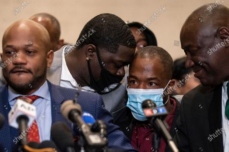 Donald Williams, a witness in the murder trial against former Minneapolis police Officer Derek Chauvin in the killing of George Floyd, center right, leans toward Brandon Williams, nephew of Floyd, center left, during a news conference after Chauvin's conviction, in Minneapolis