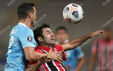 Eder Citadin of Brazil's Sao Paulo, right, and Alejandro Gonzalez of Peru's Sporting Cristal battle for the ball during a Copa Libertadores soccer match at the National Stadium in Lima, Peru
