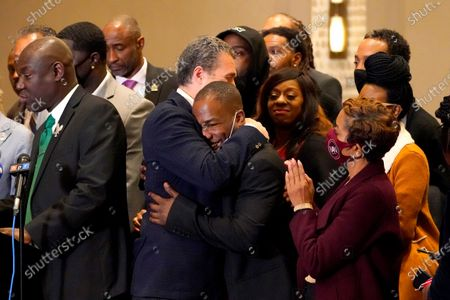 Attorney Tony Romanucci, center left, hugs Donald Williams, a key witness in the trial of former Minneapolis police Officer Derek Chauvin, during a news conference after the guilty verdict was read, in Minneapolis