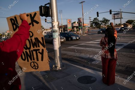 Joyce Robertson, right, clenches her fist at the intersection of Florence and Normandie Avenues in Los Angeles, after a guilty verdict was announced at the trial of former Minneapolis police Officer Derek Chauvin for the 2020 death of George Floyd