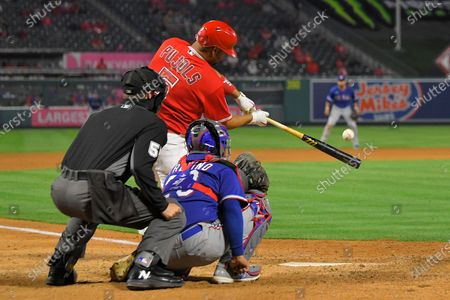 Los Angeles Angels' Albert Pujols, center hits a solo home run as Texas Rangers catcher Jose Trevino, right and home plate umpire Brennan Miller watches during the seventh inning of a baseball game, in Anaheim, Calif