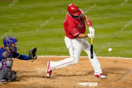 Los Angeles Angels' Albert Pujols, right, hits a solo home run as Texas Rangers catcher Jose Trevino watches during the seventh inning of a baseball game, in Anaheim, Calif