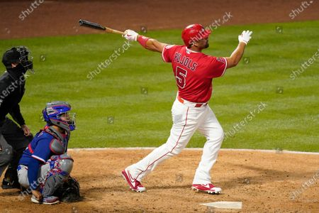 Los Angeles Angels' Albert Pujols, right, hits a solo home run as Texas Rangers catcher Jose Trevino and home plate umpire Brennan Miller watch during the seventh inning of a baseball game, in Anaheim, Calif