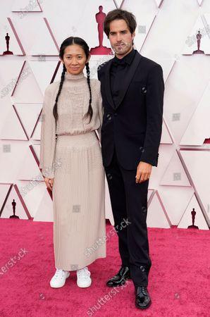 Chloe Zhao, left, and Joshua James Richards arrive at the Oscars