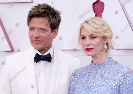 Thomas Vinterberg, left, and Helene Reingaard Neumann arrive at the Oscars