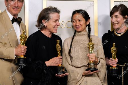 """Producers Peter Spears, from left, Frances McDormand, Chloe Zhao and Mollye Asher, winners of the award for best picture for """"Nomadland,"""" pose in the press room at the Oscars"""