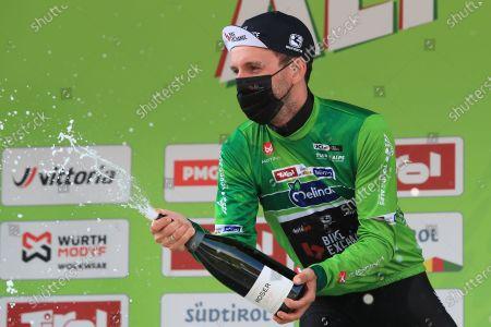 Simon Yates Team BikeExchange celebrates holding onto the tour leaders jersey with spumante; Cycling Tour des Alpes Stage 4, Naturns/Naturno to Pieve di Bono, Italy on 22nd.