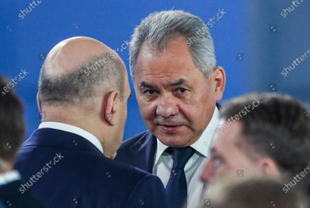 Stock Image of Russian Prime Minister Mikhail Mishustin (L) speaks with Russian Defence Minister Sergey Shoygu (C), during Russian President Vladimir Putin annual address to the Federal Assembly at the Manezh Central Exhibition Hall in Moscow, Russia, 21 April 2021. About 1,100 people including lawmakers of Russian two-chamber parliament, Government members, heads of the Constitutional and Supreme courts, and regional governors, were invited to attend the event. About 435 Russian and foreign journalists were accredited to cover the event.