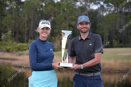 Jessica Korda holds the championship trophy on the 18th green after winning in a one-hole playoff against Danielle Kang during the final round of the Tournament of Champions LPGA golf tournament, in Lake Buena Vista, Fla. Holding the trophy with Korda is Mardy Fish, right, winner of the celebrity division