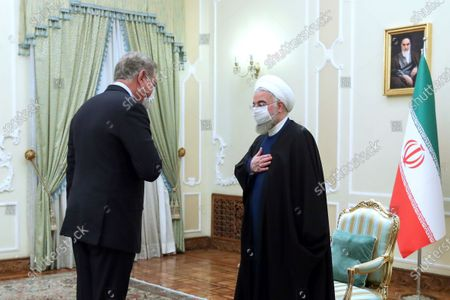 In this photo released by the official website of the office of the Iranian Presidency, Iranian President Hassan Rouhani, right, welcomes Pakistan's Foreign Minister Shah Mahmood Qureshi, for their meeting in Tehran, Iran