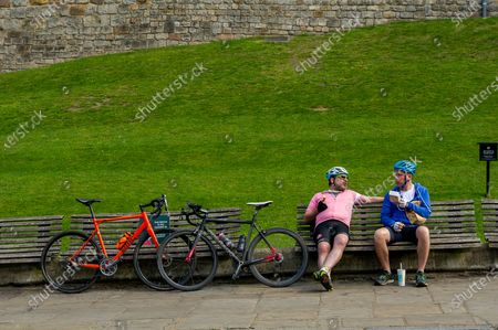 Cyclists having their lunch outside Windsor Castle. Queen Elizabeth II is spending her 95th Birthday at Windsor Castle today following the sad passing of her husband HRH Prince Philip, the Duke of Edinburgh. The ceremonial Royal Standard was flying on Windsor Castle, however, the town was very quiet this morning