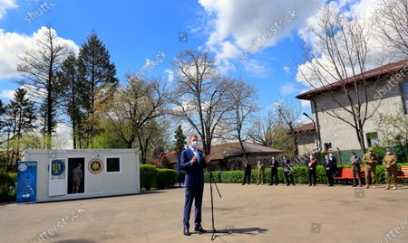 Romanian President Klaus Iohannis (C) gestures during an inauguration event held in front of the mobile vaccination center (background left), installed in the yard of the public school of Afumati village, near Bucharest, Romania, 21 April 2020. Starting from 21 April, the Romanian Army launched 20 new mobile vaccination centers against COVID-19 throughout the country, in order to speed-up the vaccination campaign in isolated or hard to reach localities. Mobile vaccination centers are serviced by military medical personnel, and assisted by civilian paramedics. Romanian authorities hope to reach 100,000 vaccinations a day.