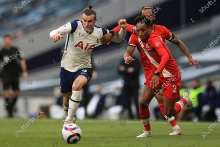 Tottenham's Gareth Bale, left gets past Southampton's Kyle Walker-Peters, front right and Theo Walcott during an English Premier League soccer match between Tottenham Hotspur and Southampton at the Tottenham Hotspur Stadium in London, England