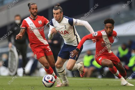 Tottenham's Gareth Bale, centre gets past Southampton's Theo Walcott, left and Kyle Walker-Peters during an English Premier League soccer match between Tottenham Hotspur and Southampton at the Tottenham Hotspur Stadium in London, England