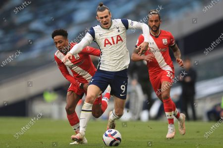 Tottenham's Gareth Bale, centre gets past Southampton's Kyle Walker-Peters, left and Theo Walcott during an English Premier League soccer match between Tottenham Hotspur and Southampton at the Tottenham Hotspur Stadium in London, England