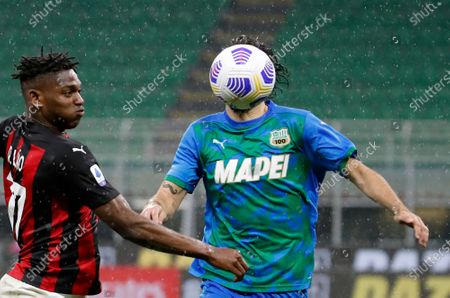 Milan's Rafael Leao, left, duels for the ball with Sassuolo's Gian Marco Ferrari during the Serie A soccer match between AC Milan and Sassuolo at the San Siro stadium, in Milan, Italy