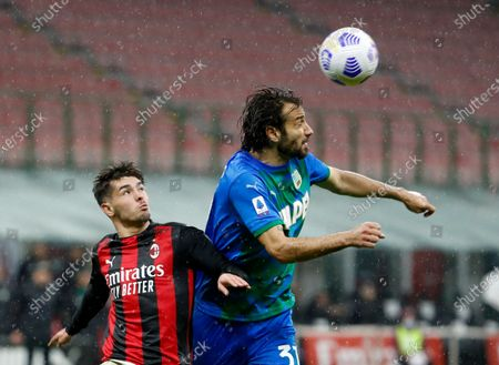 Milan's Brahim Diaz, left, duels for the ball with Sassuolo's Gian Marco Ferrari during the Serie A soccer match between AC Milan and Sassuolo at the San Siro stadium, in Milan, Italy