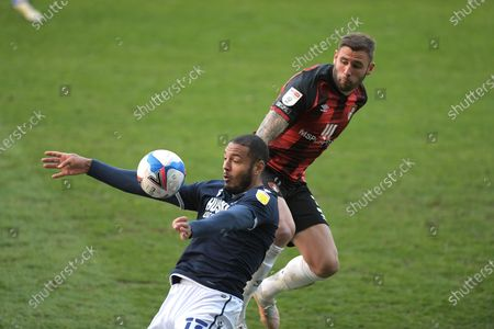 Kenneth Zohore of Millwall and Steve Cook of Bournemouth clash midfield during the Millwall vs AFC Bournemouth, EFL Championship Football match at the New Den London held behind closed doors.