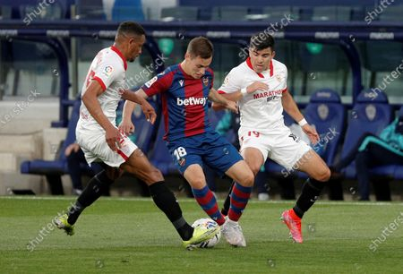 Levante's winger Jorge De Frutos (C) vies for the ball against Sevilla's midfielder Fernando Reges (L) and Marcos Acuna (R) during the Spanish LaLiga soccer match between Levante UD and Sevilla CF at Ciutat de Valencia stadium in Valencia, eastern Spain, 21 April 2021.