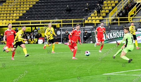 Dortmund's Raphael Guerreiro, second from left, shoots to score his side's second goal during the German Bundesliga soccer match between Borussia Dortmund and Union Berlin in Dortmund, Germany