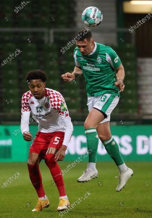 Mainz's Jean-Paul Boetius (L) in action against Bremen's Milos Veljkovic (R) during the German Bundesliga soccer match between SV Werder Bremen and FSV Mainz 05 in Bremen, Germany, 21 April 2021.