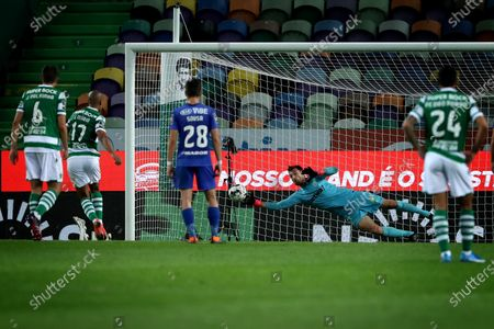Belenenses SAD's goalkeeper Stanislav Kritciuk makes a safe of the penalty kick by Joao Mario of Sporting CP during the Portuguese League football match between Sporting CP and Belenenses SAD at Jose Alvalade stadium in Lisbon, Portugal on April 21, 2021.