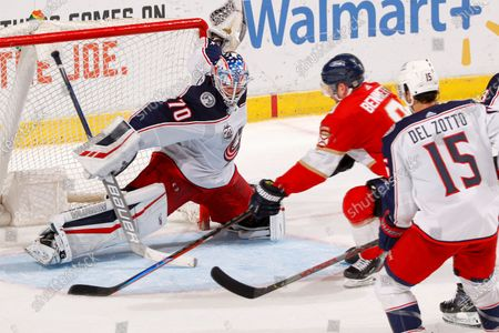 Columbus Blue Jackets defenseman Michael Del Zotto (15) looks on as Columbus Blue Jackets goaltender Joonas Korpisalo (70) stops a shot by Florida Panthers center Sam Bennett (9) during the third period of an NHL hockey game, in Sunrise, Fla