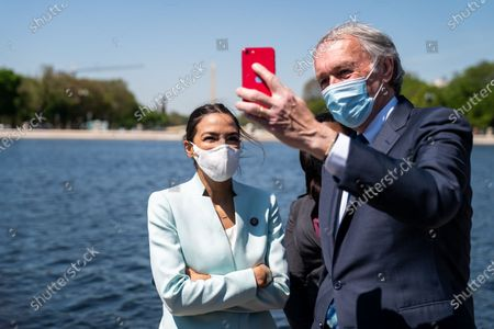 Rep. Alexandria Ocasio-Cortez (D-NY), Sen. Ed Markey (D-MA), and Rep. Cori Bush (D-MO) record a video following a news conference to reintroduce the Green New Deal and introduce the Civilian Climate Corps Act at the Capitol Reflecting Pool near the West Front of the U.S. Capitol Building on Tuesday, April 20, 2021 in Washington, DC. (Kent Nishimura / Los Angeles Times)