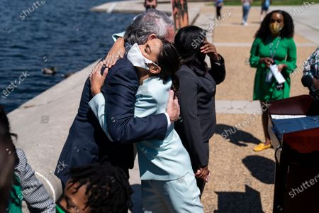 Rep. Alexandria Ocasio-Cortez (D-NY) hugs Sen. Ed Markey (D-MA) following a news conference to reintroduce the Green New Deal and introduce the Civilian Climate Corps Act at the Capitol Reflecting Pool near the West Front of the U.S. Capitol Building on Tuesday, April 20, 2021 in Washington, DC. (Kent Nishimura / Los Angeles Times)