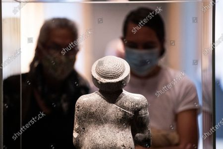 Visitors look at a statue of Prince Gudea in the exhibition 'Mesopotamia: Civilization Begins' at the J. Paul Getty Museum as the Getty Villa reopens to the public after being closed due to the coronavirus pandemic in Los Angeles, California, USA, 21 April 2021. The exhibition runs from April 21 to August 16, 2021.