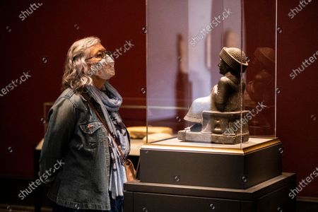 Stock Image of A visitor looks at a statue of Prince Gudea in the exhibition 'Mesopotamia: Civilization Begins' at the J. Paul Getty Museum as the Getty Villa reopens to the public after being closed due to the coronavirus pandemic in Los Angeles, California, USA, 21 April 2021. The exhibition runs from April 21 to August 16, 2021.