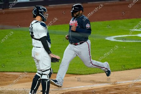 Atlanta Braves' Pablo Sandoval scores on Ehire Adrianza's fifth-inning sacrifice fly, next to New York Yankees catcher Gary Sanchez in a baseball game, at Yankee Stadium in New York