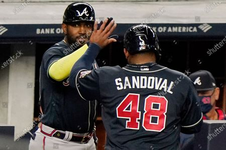 Stock Image of Atlanta Braves' Marcell Ozuna, left, greets designated hitter Pablo Sandoval (48) at the dugout steps after Sandoval scored on Ehire Ardrianza's fifth-inning sacrifice fly in a baseball game against the New York Yankees, at Yankee Stadium in New York